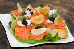 Baguette, smoked salmon, egg, caviar, orange Royalty Free Stock Photos
