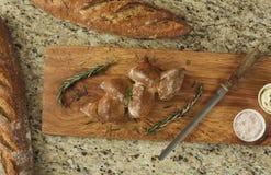 Baguette su un contatore accanto ad un tagliere con un coltello ed i condimenti Fotografia Stock