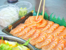 Baguette tenant un morceau de saumons Image libre de droits