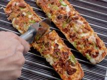 Baguette van de hand scherpe pizza met mozarella, groene paprika, ui Stock Foto