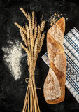Baguette, wheat and flour on black background Royalty Free Stock Images