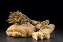 Baguette y ciabatta, pan en la tabla de madera oscura Trigo y panes mezclados frescos en fondo negro Alimento Fotos de archivo libres de regalías