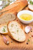 Baguette z ziele, olejem, pikantność i czosnkiem na drewnianej desce, Fotografia Stock