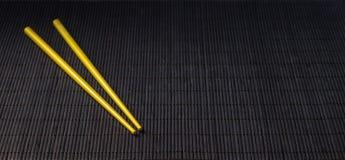 Baguettes de sushi sur le tapis de paille de bambou noir Image stock
