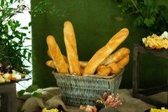 Baguettes del pan en cesta en el banquete greenery imágenes de archivo libres de regalías