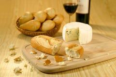 Baguettes en una cesta, un queso y un vino Fotos de archivo