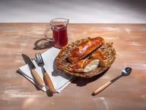 Baguettes en una placa decorativa, jarabe en un jarro de cristal, cubiertos en un fondo marrón foto de archivo libre de regalías