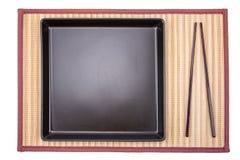 Baguettes et plat noir sur le bambou Photographie stock libre de droits