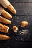 Baguettes françaises avec la graine de sésame sur le fond en bois noir Photos libres de droits