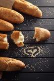 Baguettes françaises avec la graine de sésame sur le fond en bois noir Photographie stock libre de droits