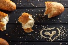 Baguettes françaises avec la graine de sésame sur le fond en bois noir Image libre de droits