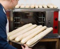Baguettes hermosos alegres sonrientes de la hornada del hombre Imagenes de archivo