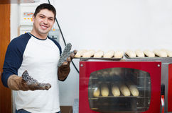 Baguettes hermosos alegres sonrientes de la hornada del hombre Fotografía de archivo libre de regalías