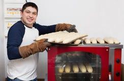 Baguettes hermosos sonrientes de la hornada del hombre Imágenes de archivo libres de regalías