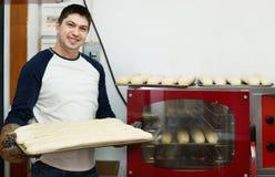 Baguettes hermosos sonrientes de la hornada del hombre Foto de archivo