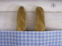 Baguettes under plaid cloth. Baguettes under a white and blue plaid cloth Royalty Free Stock Image
