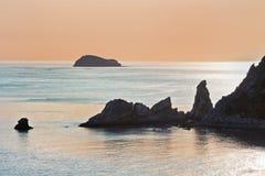 Bahía con las rocas de forma irregular en la puesta del sol imagen de archivo