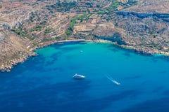 Bahía de Mgiebah, ensenada aislada accesible por una trayectoria escarpada, rocosa, con una playa arenosa y un agua de azules tur fotografía de archivo
