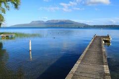 Bahía de Rangiuru, lago Tarawera, Nueva Zelanda Embarcadero y una visión a través para montar Tarawera fotos de archivo libres de regalías
