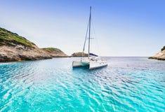 Bahía hermosa con el catamarán del barco de navegación, isla de Córcega, Francia imágenes de archivo libres de regalías