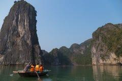 Bahía larga de la ha, Vietnam - 24 de diciembre de 2013: turistas en un bote pequeño Fotos de archivo
