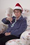 Bah Humbug Mature Senior Woman No Christmas Spirit. A humorous look at Christmas. A mature senior woman gives a thumbs down to Christmas spirit and the season Stock Photography