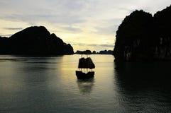 Bahía de Halong, barco de los desperdicios de Hanoi durante puesta del sol Fotos de archivo libres de regalías