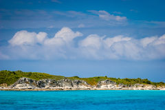 Bahama blue seperated by a while green island. Large, white clouds in a blue sky sit over a white and green spit of land framed by the brilliant blue water stock images