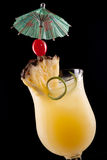 Bahama Mama Cocktail. Over black background on reflection surface, garnished with pineapple flag, maraschino cherry, and lime twist. Most popular cocktails Royalty Free Stock Image