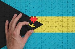 Bahamas flag is depicted on a puzzle, which the man`s hand completes to fold.  vector illustration