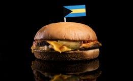 Bahamas flagga överst av hamburgaren som isoleras på svart Royaltyfria Foton