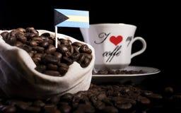 Bahamas flagga i en påse med kaffebönor som isoleras på svart Royaltyfri Foto