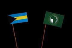 Bahamas flagga med afrikanska unionenflaggan som isoleras på svart Arkivbild