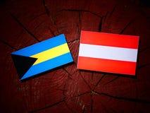 Bahamas flagga med den österrikiska flaggan på en trädstubbe Royaltyfri Foto