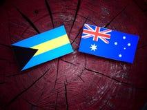 Bahamas flagga med den australiska flaggan på en isolerad trädstubbe Royaltyfri Foto
