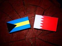 Bahamas flagga med den bahrainska flaggan på en isolerad trädstubbe Arkivbilder