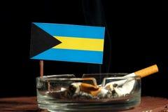 Bahamas flagga med den brinnande cigaretten i askfatet som isoleras på svart Arkivbilder
