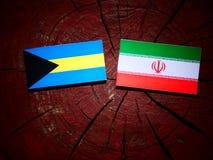 Bahamas flagga med den iranska flaggan på en isolerad trädstubbe Arkivfoto