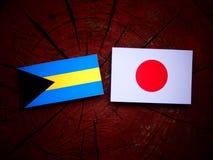 Bahamas flagga med den japanska flaggan på en isolerad trädstubbe Arkivfoto