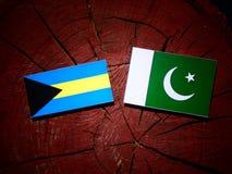 Bahamas flagga med den Pakistan flaggan på en isolerad trädstubbe Arkivfoto