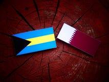 Bahamas flagga med den Qatari flaggan på en isolerad trädstubbe Arkivfoton