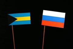 Bahamas flagga med den ryska flaggan som isoleras på svart Royaltyfria Foton