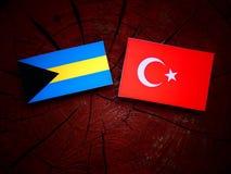 Bahamas flagga med den turkiska flaggan på en trädstubbe Royaltyfri Fotografi