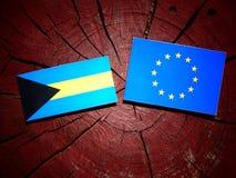 Bahamas flagga med EU-flaggan på en isolerad trädstubbe Arkivfoto