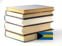Bahamas flagga med högen av böcker på vit bakgrund Royaltyfri Foto