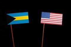 Bahamas flagga med USA flaggan som isoleras på svart Arkivfoto