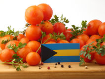 Bahamas flagga på en träpanel med tomater som isoleras på en vit Royaltyfria Foton