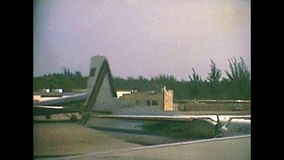Bahamas Nassau airport. Airplane landing in Lynden Pindling international airport of Nassau , capital town of Bahamas in 70`s with old buildings. Historical stock video