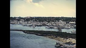 Bahamas Nassau harbour. In New Providence island coastline with fishing boats and yacht in 70`s. The historical Bahamas in 1978 stock video