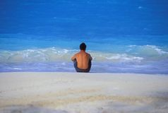 Bahamas Tropics 01. Tropical photo of Bahamas, Beautiful blue water, white sands, man sitting alone looking out to ocean Stock Photo
